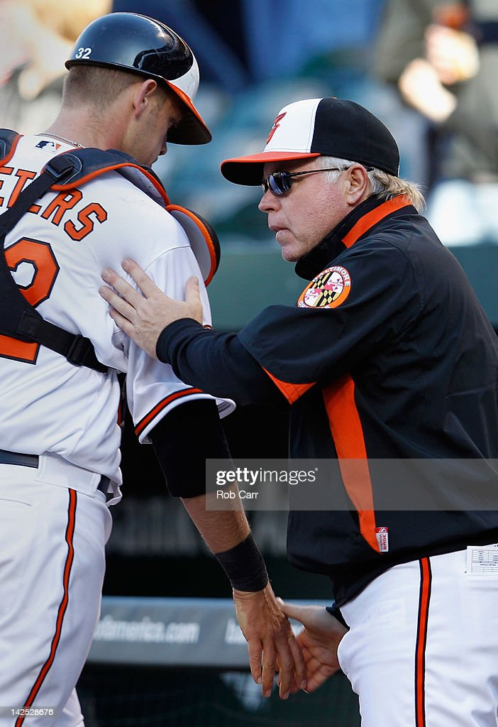 Manager Buck Showalter congratulates catcher Matt Wieters #32 after the Orioles defeated the Minnesota Twins 4-2 during opening day at Oriole Park at Camden Yards on April 6, 2012 in Baltimore, Maryland.