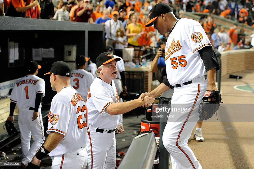 Manager Buck Showalter of the Baltimore Orioles celebrates with Alfredo Simon #55 after a 6-3 victory against the Los Angeles Angels of Anaheim at Camden Yards on August 3, 2010 in Baltimore, Maryland.