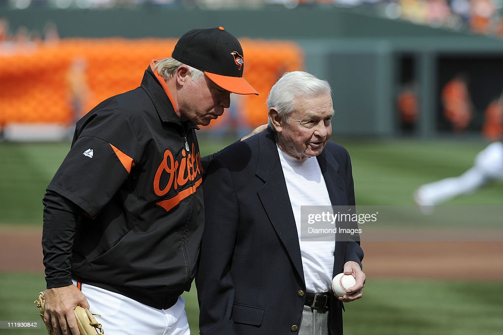 Manager Buck Showalter #26 of the Baltimore Orioles escorts former manager and Hall of Famer Earl Weaver from the field after Weaver threw out the ceremonial first pitch prior to the Opening Day game on April 4, 2011 against the Detroit Tigers at Oriole Park in Baltimore, Maryland.