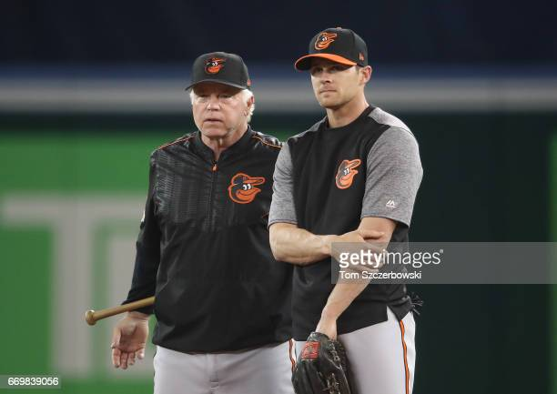 Manager Buck Showalter of the Baltimore Orioles talks to Craig Gentry during batting practice before the start of MLB game action against the Toronto...