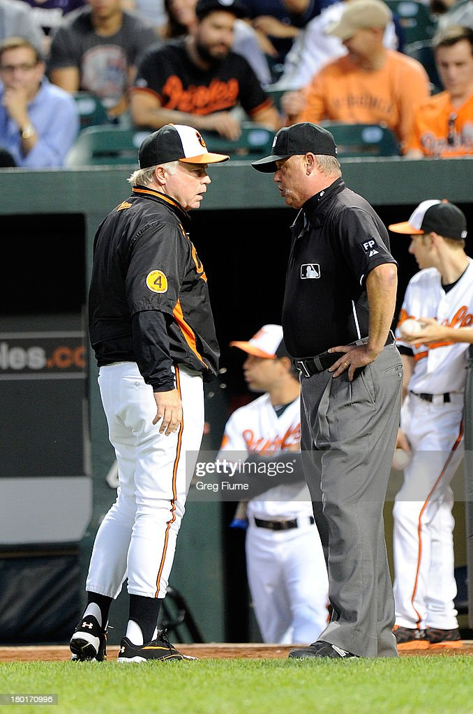 Manager Buck Showalter #26 of the Baltimore Orioles talks with first base umpire Jim Joyce in the first inning after an altercation with the New York Yankees at Oriole Park at Camden Yards on September 9, 2013 in Baltimore, Maryland.