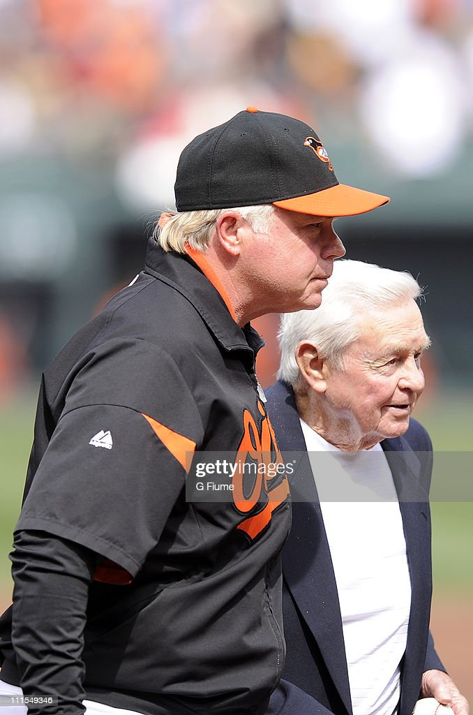 Manager Buck Showalter #26 of the Baltimore Orioles talks with former Orioles manager Earl Weaver (R) after Weaver threw out the ceremonial first pitch before the opening day game against the Detroit Tigers at Camden Yards on April 4, 2011 in Baltimore, Maryland.