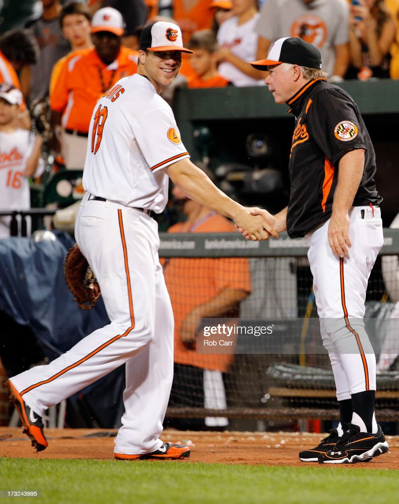Manager Buck Showalter shakes hands with Chris Davis #19 of the Baltimore Orioles following the Orioles 6-1 win over the Texas Rangers at Oriole Park at Camden Yards on July 10, 2013 in Baltimore, Maryland.