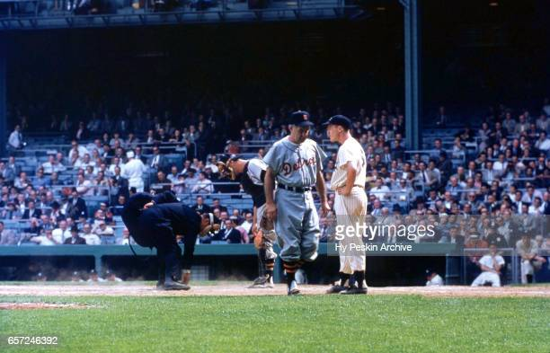 Manager Bucky Harris of the Detroit Tigers walks back to the dugout after arguing a call as Andy Carey of the New York Yankees waits to bat during an...