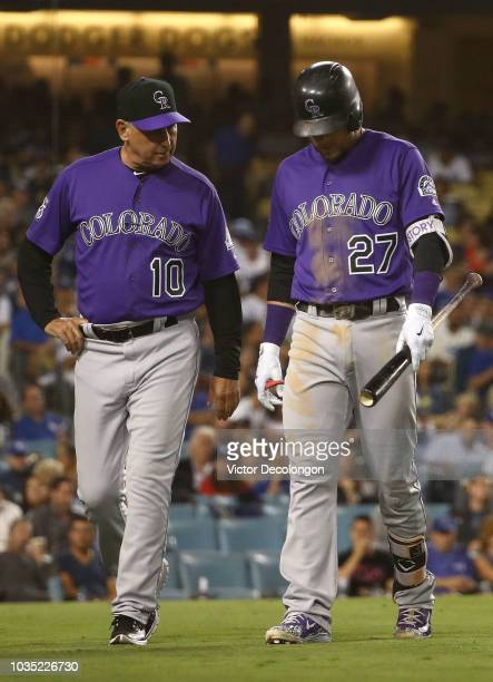 Manager Bud Black of the Colorado Rockies walks with Trevor Story back to the dugout after Story left his atbat injured and replaced by Pat Valaika...
