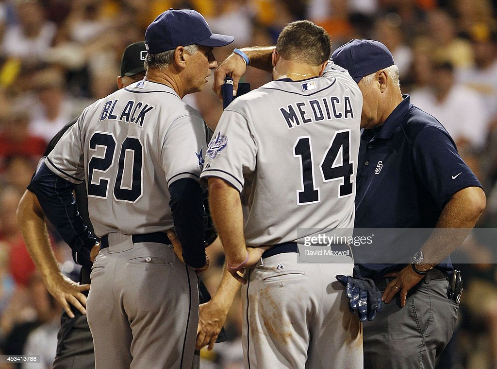 Manager Bud Black #20 of the San Diego Padres talks with Tommy Medica #14 after Medica was hit in the helmet with a pitch during the eighth inning of their game against the Pittsburgh Pirates on August 9, 2014 at PNC Park in Pittsburgh, Pennsylvania. The Padres defeated the Pirates 2-1.