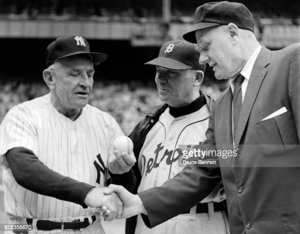 Manager Casey Stengel of the New York Yankees is congratulated by umpire Edwin A Rommel and manager Jimmy Dykes of the Detroit Tigers as he holds up...