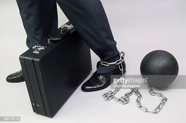 Manager chained to a metal weight Symbolic image for white collar crime