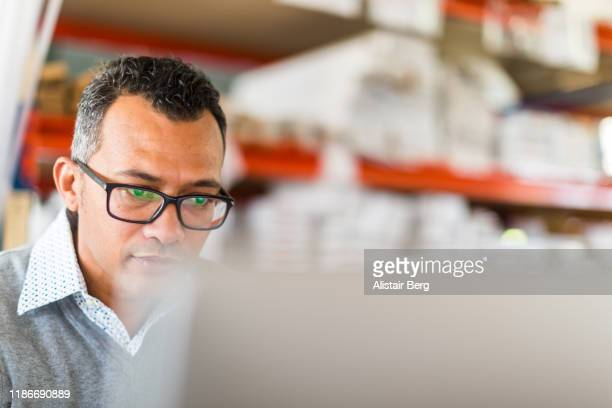 manager checking stock on a computer in a busy small warehouse - small business stock pictures, royalty-free photos & images