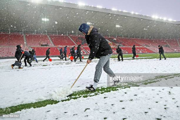 Manager Chris Coleman helps as Sunderland staff clear the pitch to enable first team training at Stadium of Light on March 1 2018 in Sunderland...