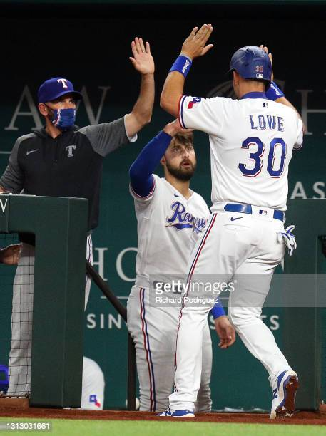 Manager Chris Woodward and Joey Gallo of the Texas Rangers greet Nate Lowe who scored on a single by David Dahl against the Baltimore Orioles in the...