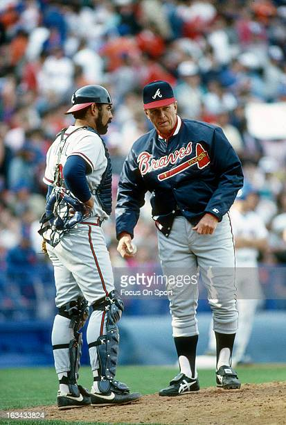 Manager Chuck Tanner of the Atlanta Braves talks with catcher Ozzie Virgil while making a pitching change during an Major League Baseball game circa...