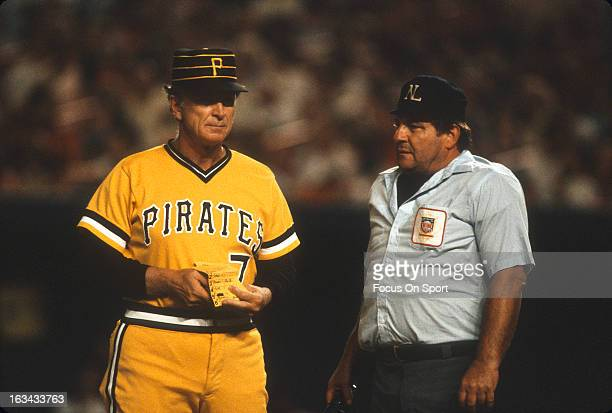 Manager Chuck Tanner of the Pittsburgh Pirates walks back towards the dugout after making a change in his lineup with the homeplate umpire during an...