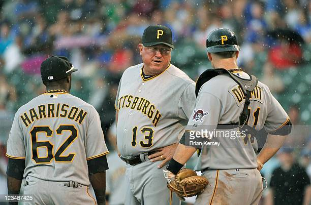 Manager Clint Hurdle of the Pittsburgh Pirates stands on the mound with third baseman Josh Harrison and catcher Ryan Doumit during the seventh inning...