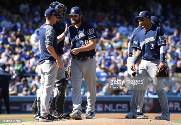 Manager Craig Counsell of the Milwaukee Brewers takes out starting pitcher Wade Miley as Orlando Arcia looks on after Miley faced only one batter...