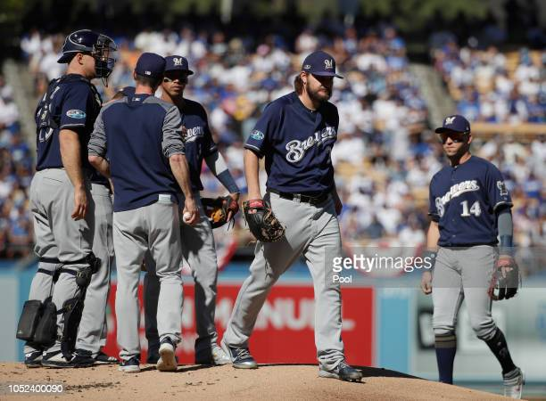 Manager Craig Counsell of the Milwaukee Brewers takes out starting pitcher Wade Miley as Hernan Perez looks on after Miley faced only one batter...