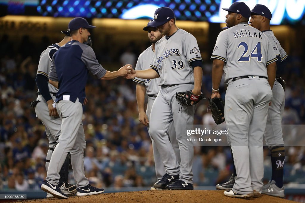 Manager Craig Counsell of the Milwaukee Brewers takes the ball from relief pitcher Corbin Burnes #39 in the seventh inning during the MLB game against the Los Angeles Dodgers at Dodger Stadium on August 1, 2018 in Los Angeles, California.