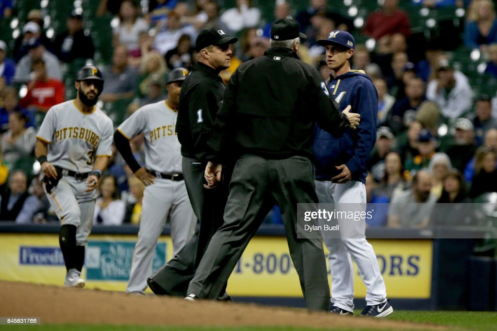 Manager Craig Counsell of the Milwaukee Brewers talks with umpires Bruce Dreckman and Bill Welke in the fourth inning against the Pittsburgh Pirates at Miller Park on September 11, 2017 in Milwaukee, Wisconsin.
