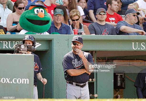 Manager Craig Kimbrel of the Atlanta Braves is watched by Boston Red Sox mascot Wally The Green Monster during the seventh inning of Boston's 94 win...