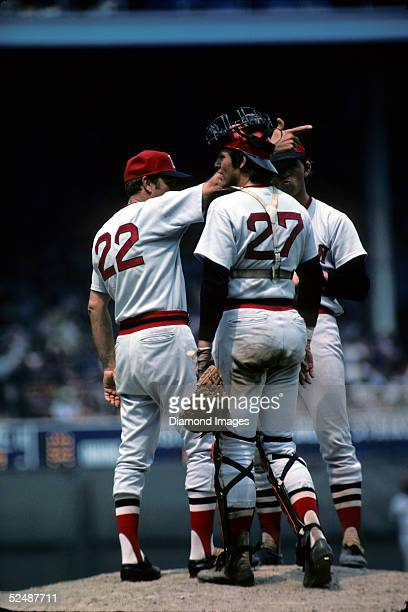 Manager Darrell Johnson, catcher Carlton Fisk and pitcher Bill Lee of the Boston Red Sox talk on the mound as Johnson signals for the relief pitcher...