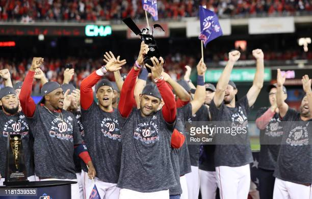 Manager Dave Martinez of the Washington Nationals celebrates with the trophy after winning game four and the National League Championship Series...