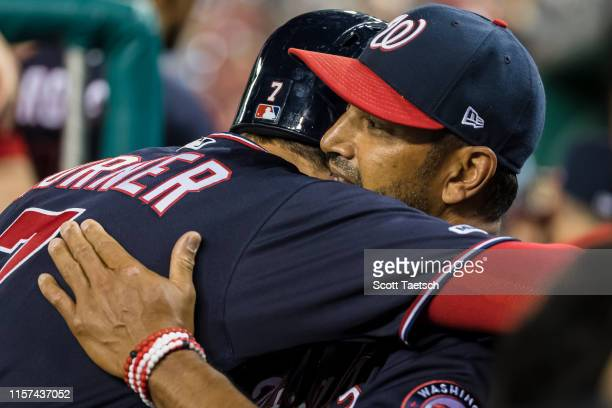Manager Dave Martinez of the Washington Nationals congratulates Trea Turner for hitting the cycle against the Colorado Rockies during the seventh...