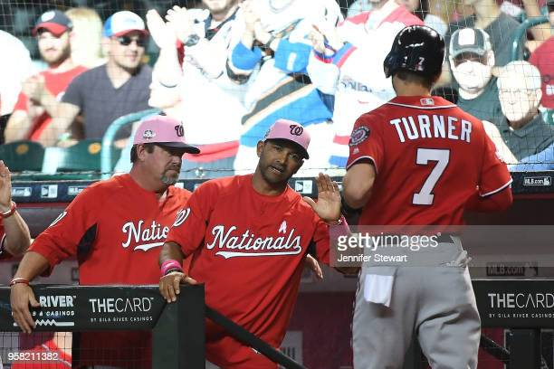 Manager Dave Martinez of the Washington Nationals congratulates Trea Turner after scoring against the Arizona Diamondbacks in the first inning of the...