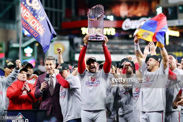 Manager Dave Martinez of the Washington Nationals hoists the Commissioners Trophy after defeating the Houston Astros 6-2 in Game Seven to win the...