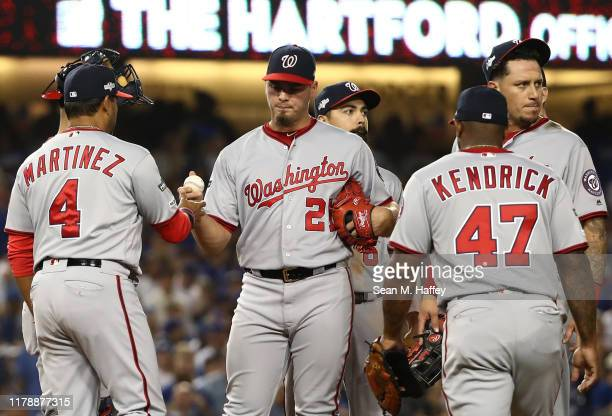Manager Dave Martinez of the Washington Nationals relieves starting pitcher Tanner Rainey during the seventh inning of game one of the National...