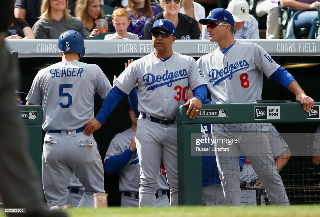 Manager Dave Roberts #30 and bench coach Bob Geren #8 of the Los Angeles Dodgers congratulate Corey Seager #5 on scoring a run in the third inning of a regular season MLB game between the Colorado Rockies and the visiting Los Angeles Dodgers at Coors Field on October 1, 2017 in Denver, Colorado.