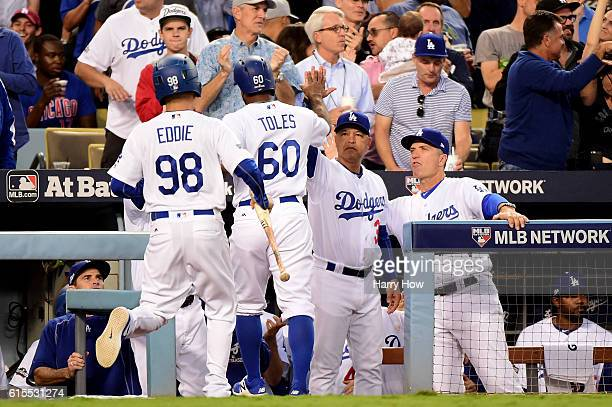 Manager Dave Roberts celebrates with Andrew Toles of the Los Angeles Dodgers after he scores a run in the third inning on a hit by Corey Seager...
