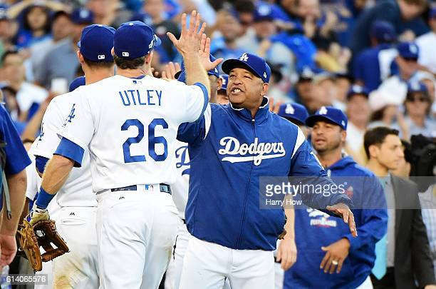 Manager Dave Roberts celebrates with Chase Utley of the Los Angeles Dodgers afte rthey defeated the Washington Nationals 6 to 5 during game four of...