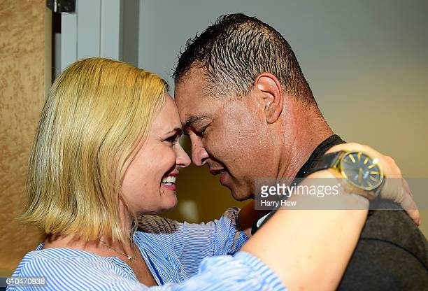 Manager Dave Roberts of the Los Angeles Dodgers celebrates a 43 win over the Colorado Rockies to clinch the National League West Division with wife...