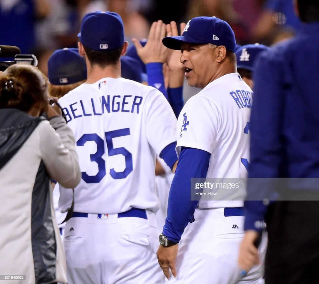 Manager Dave Roberts #30 of the Los Angeles Dodgers celebrates a 6-4 win over the Minnesota Twins with Cody Bellinger #35 at Dodger Stadium on July 24, 2017 in Los Angeles, California.