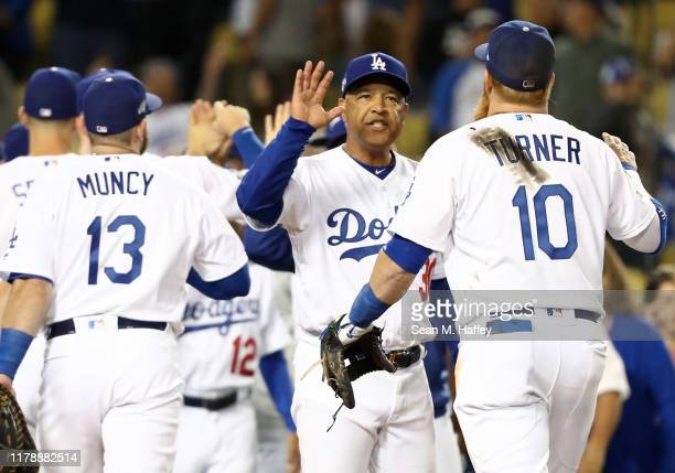 Manager Dave Roberts of the Los Angeles Dodgers celebrates with Justin Turner after the Dodgers defeated the Washington Nationals 6-0 in game one of...