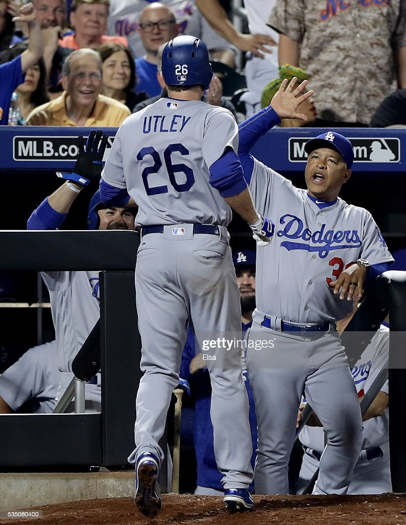 Manager Dave Roberts #30 of the Los Angeles Dodgers congratulates his player Chase Utley #26 after Utley hit a grand slam in the seventh inning against the New York Mets at Citi Field on May 28, 2016 in the Flushing neighborhood of the Queens borough of New York City.