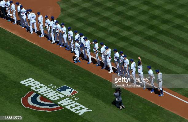 Manager Dave Roberts of the Los Angeles Dodgers is greeted by his players as they line up for an Opening Day game against Arizona Diamondbacks at...