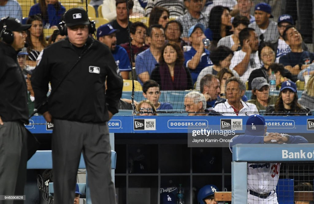 Manager Dave Roberts #30 of the Los Angeles Dodgers rests his head on the rail as he waits for a ruling on a challenge from umpire Brian Gorman #9 in the fourth inning of the game against the Arizona Diamondbacks at Dodger Stadium on April 14, 2018 in Los Angeles, California.
