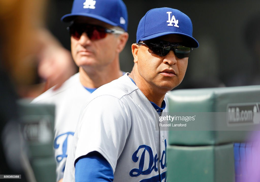 Manager Dave Roberts #30 of the Los Angeles Dodgers sits in the dugout prior to a regular season MLB game against the Colorado Rockies at Coors Field on October 1, 2017 in Denver, Colorado.