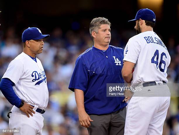 Manager Dave Roberts of the Los Angeles Dodgers visits Mike Bolsinger with a trainer during the second inning against the Milwaukee Brewers at Dodger...