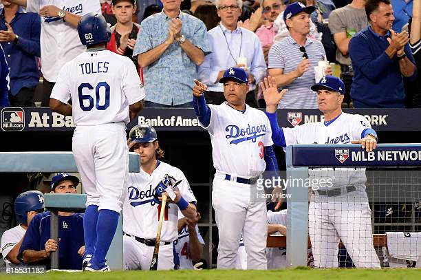 Manager Dave Roberts points at Andrew Toles of the Los Angeles Dodgers after he scores a run in the third inning on a hit by Corey Seager against the...