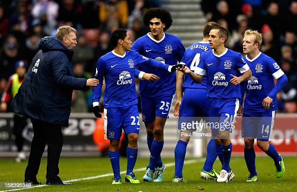 Manager David Moyes of Everton speaks to his player Steven Pienaar as he celebrates his goal with team mates during the Barclays Premier League match...