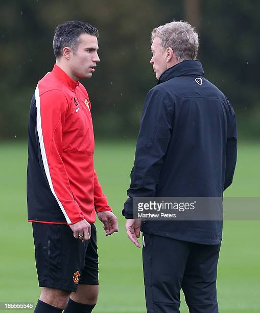 Manager David Moyes of Manchester United speaks to Robin van Persie during a first team training session, ahead of their UEFA Champions League Group...
