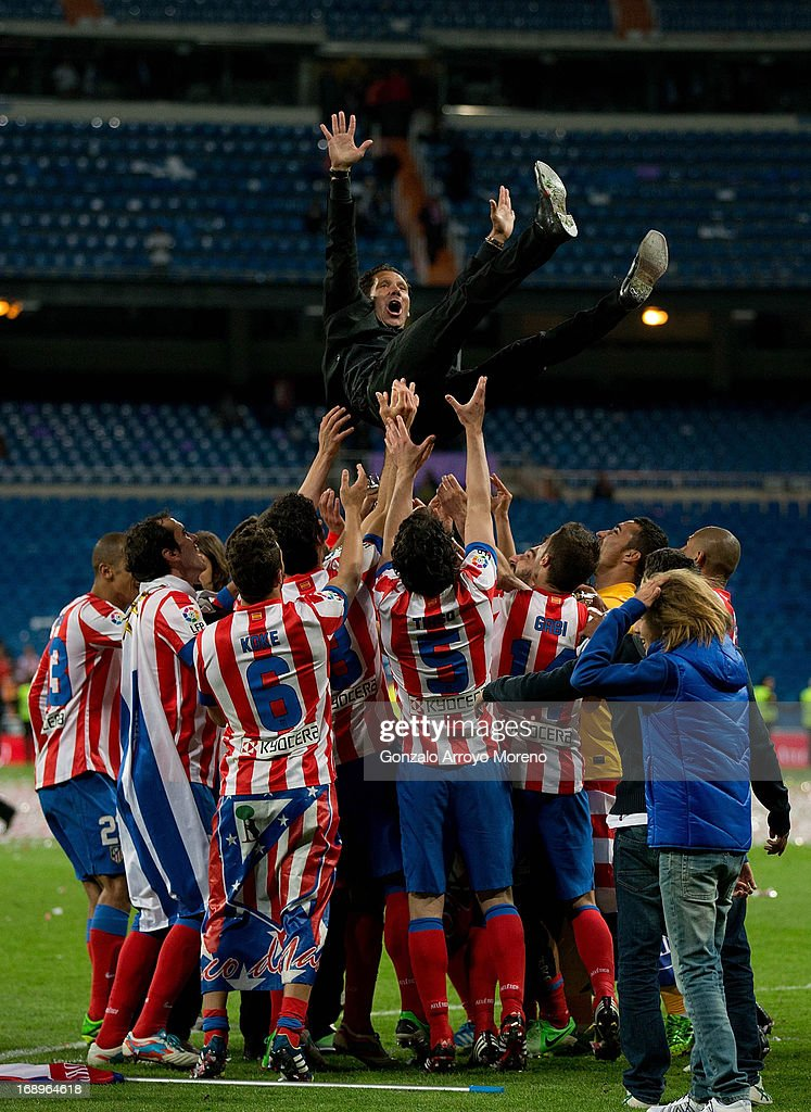 Manager Diego Pablo Simeone of Atletico de Madrid is held in the air by his teammates after winning the Copa del Rey Final match between Real Madrid CF and Club Atletico de Madrid at Estadio Santiago Bernabeu on May 17, 2013 in Madrid, Spain.