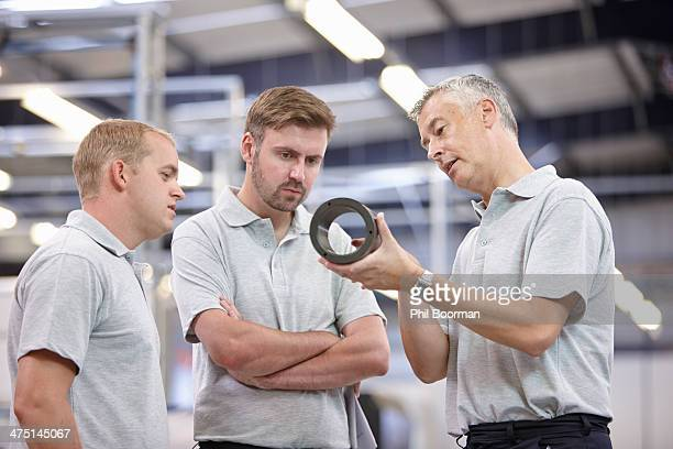 Manager discussing component in engineering factory