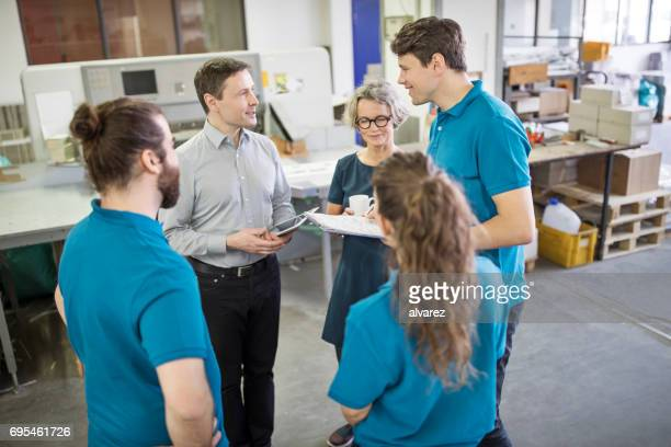 Manager discussing new printing projects with workers
