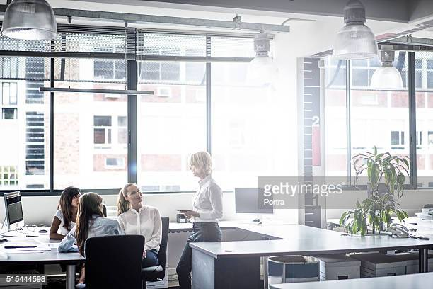 Manager discussing with executives in brightly lit office