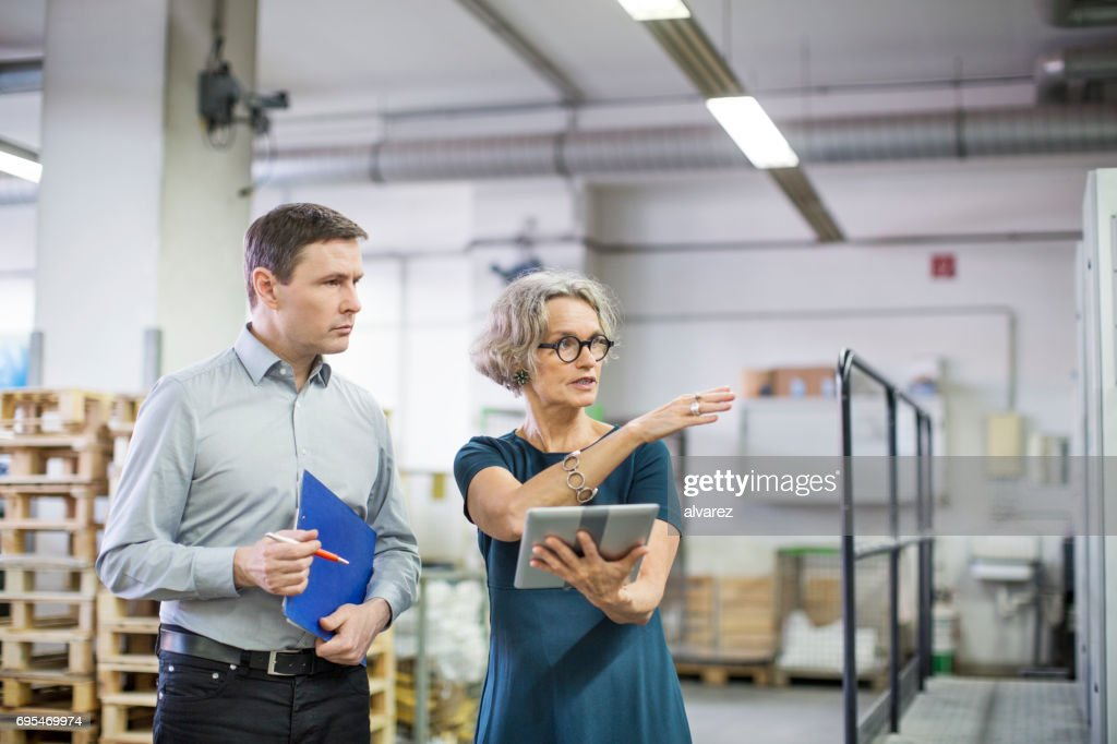 Manager discussing with male worker at printing plant : Stock Photo