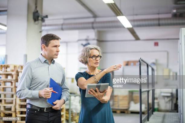 Manager discussing with male worker at printing plant