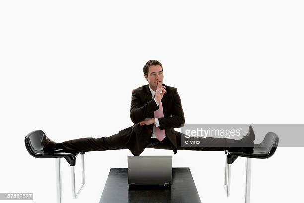 Manager doing a split between two black chairs in a suit